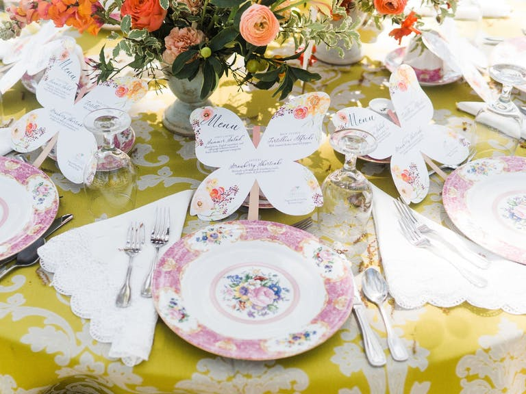 Rose-and-white tablescape with butterfly menus
