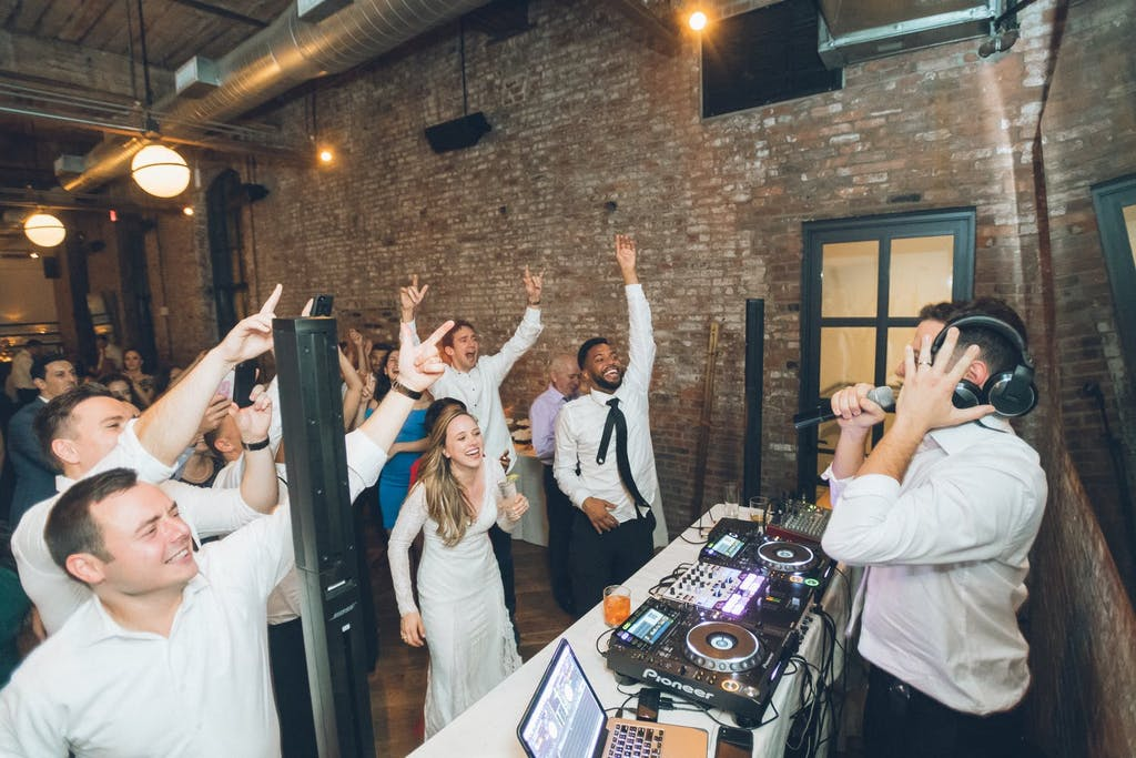 Bride and guests dancing in front of DJ