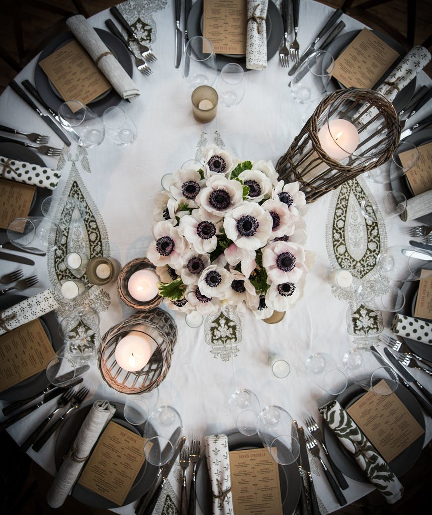 Banquet round with paisley tablecloth and whicker candle holders at a wedding rehearsal dinner   PartySlate