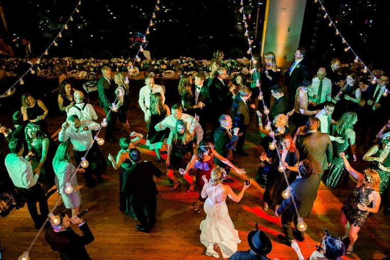 party goers dancing under stringed lights