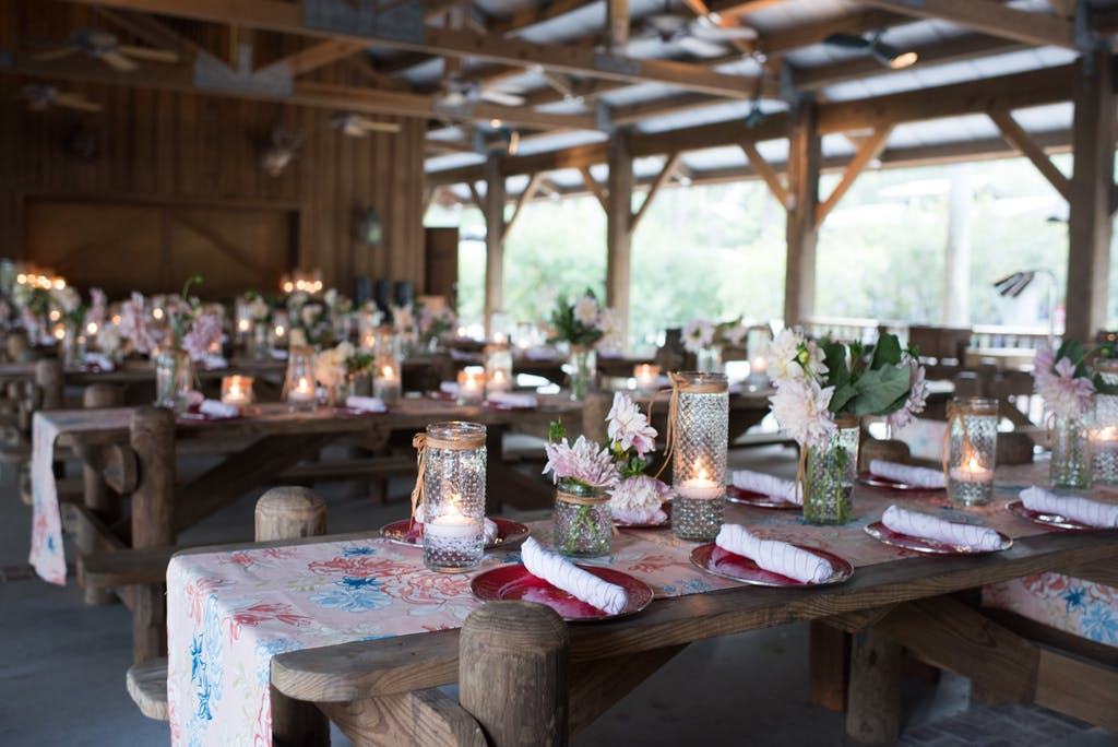Outdoor rustic space featuring wooden banquet tables with colorful linens at a wedding rehearsal dinner   PartySlate
