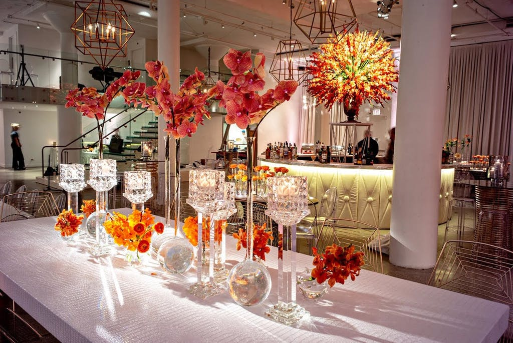 Banquet table with orange and hot pink florals at a wedding rehearsal dinner party