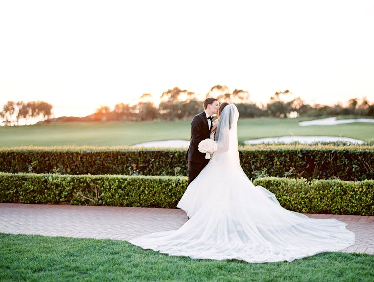 bride and groom kiss in front of gold course