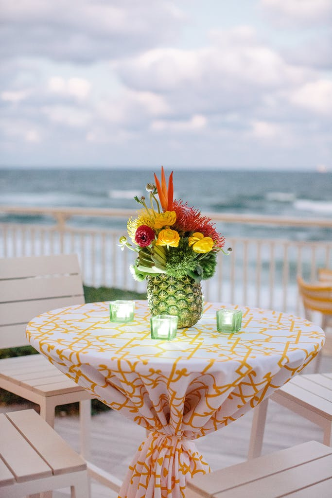 Cocktail table with green tea lights and pineapple centerpiece at a wedding rehearsal dinner party   PartySlate