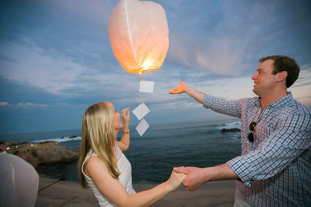 Man and woman releasing wish lantern over ocean at a wedding rehearsal dinner   PartySlate