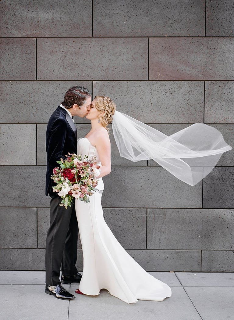 bride with wind-blown veil and groom kiss in front of gray brick wall