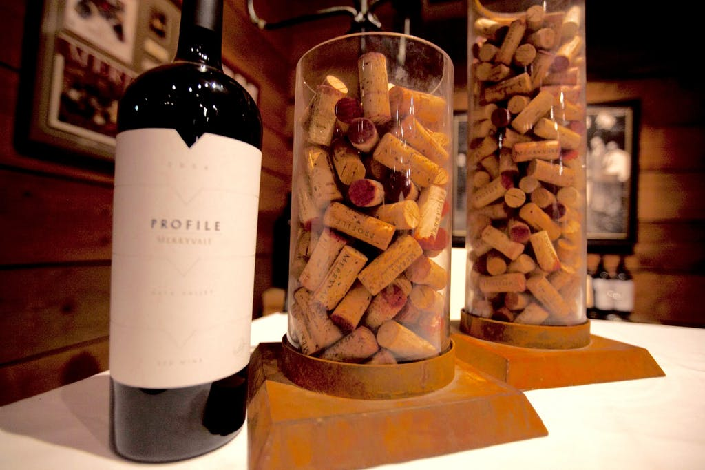 Wine bottle and clear vases filled with wine corks at a wedding rehearsal dinner   PartySlate