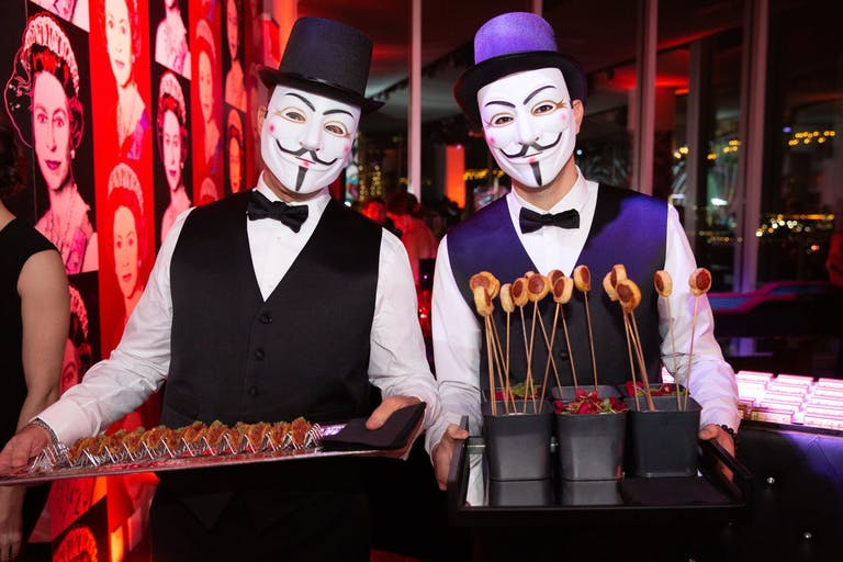 Two masked servers carrying trays of food