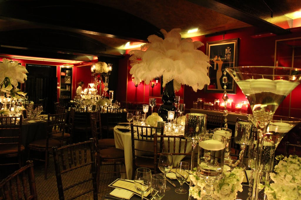 Tortoise Supper Club decorated with white feather centerpieces for Great Gatsby-themed wedding rehearsal dinner party   PartySlate