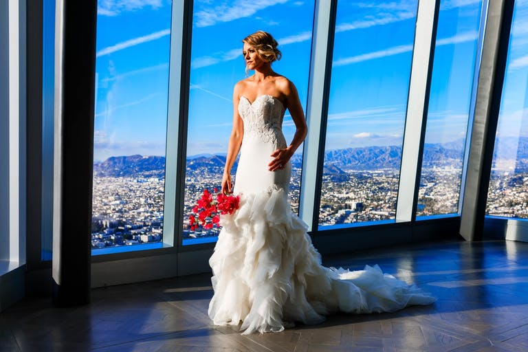 bride with vibrant red bouquet poses in front of floor-to-ceiling windows