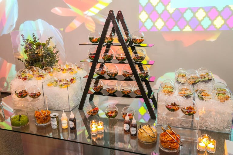 candlelit catering station with pyramid display and globed dishware