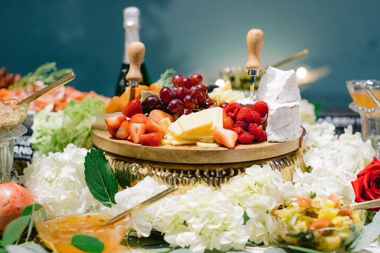 charcuterie spread surrounded by white blooms