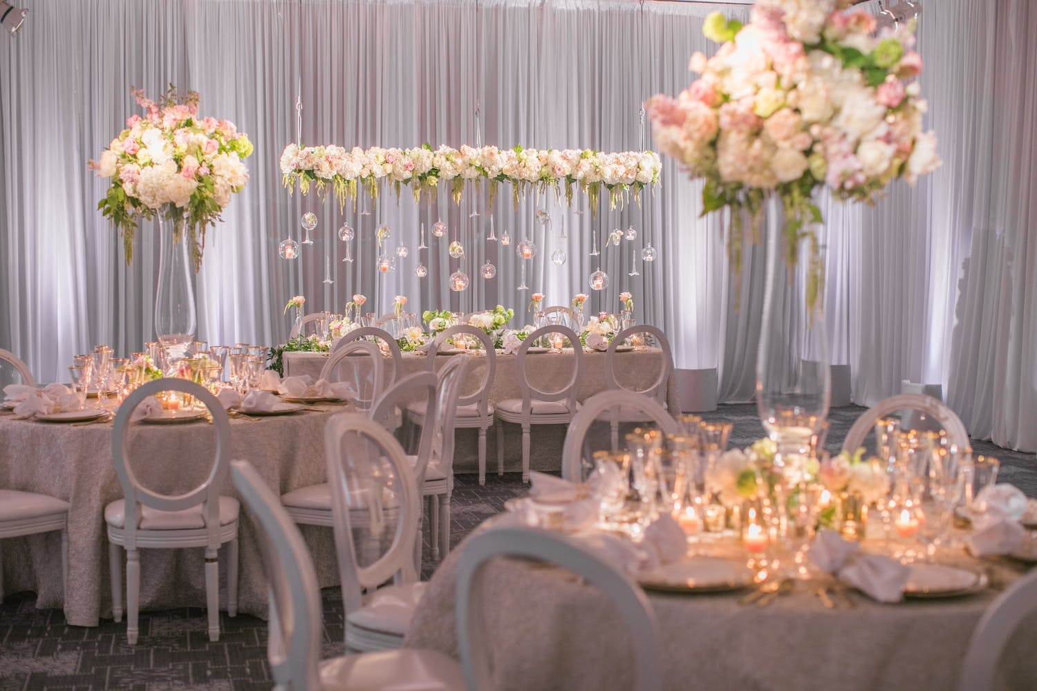 reception area with pink bloom centerpieces and suspended installations