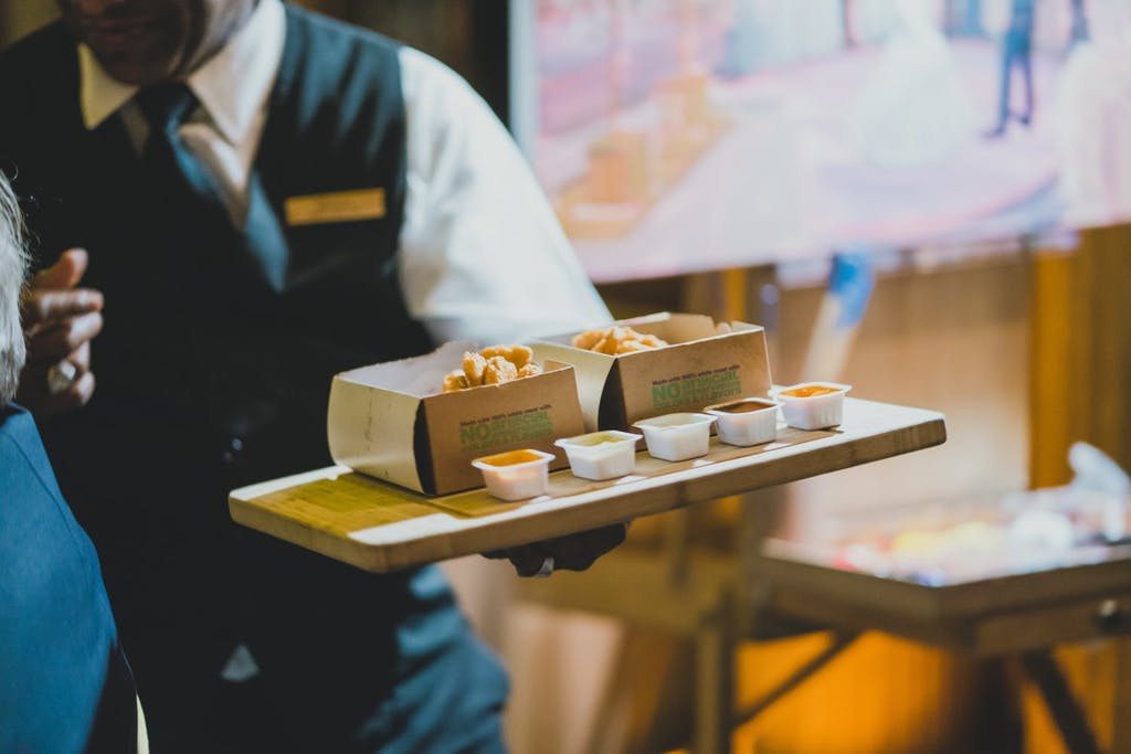 cropped photo of server and tray of small bites