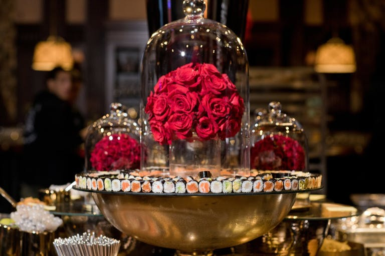 sushi display with cloche bell glass and red roses
