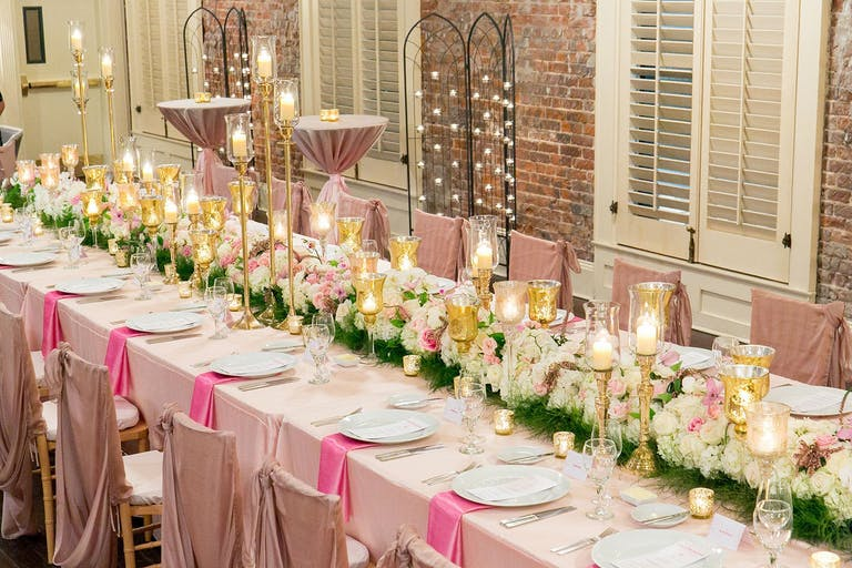 Tablescape with white floral table arrangement, blush table cloth, and bright pink napkins