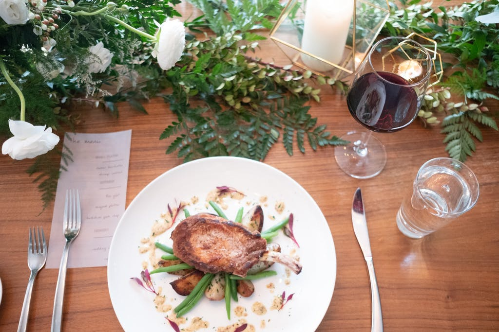 Artfully plated pork chops at a wedding rehearsal dinner   PartySlate