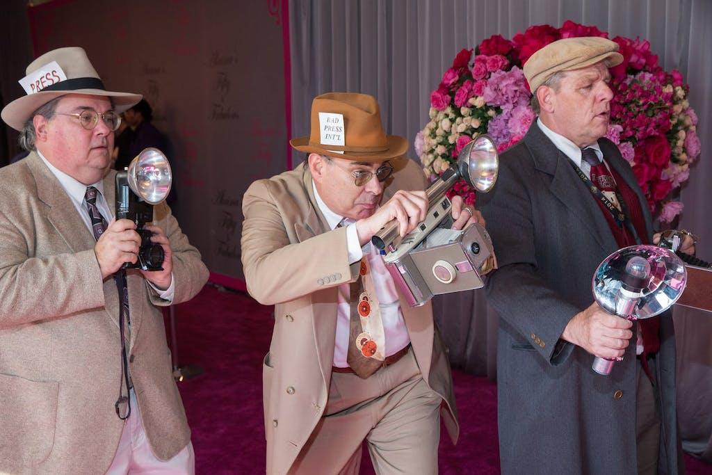 Three men dressed as paparazzi photographers