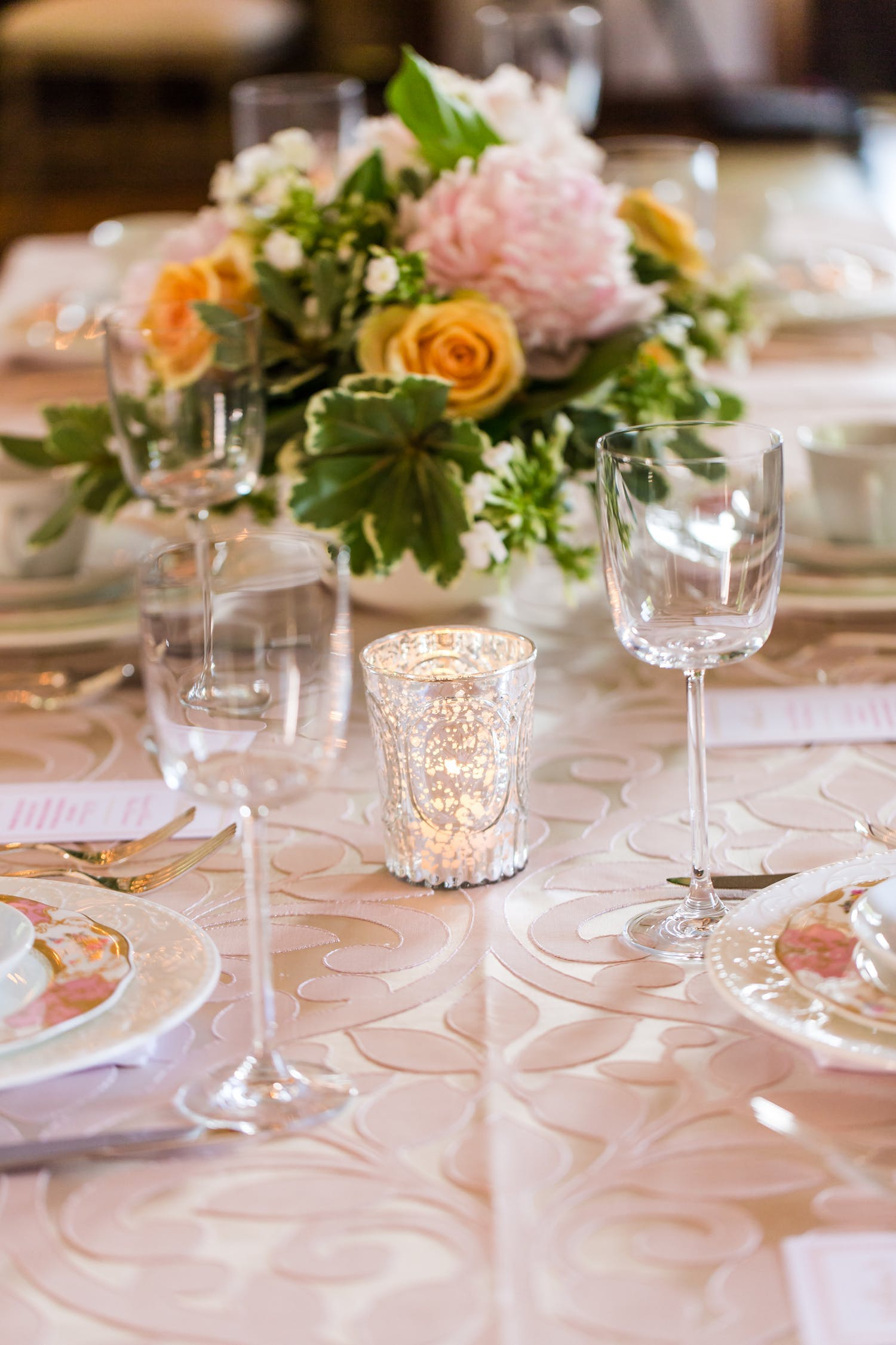 blush colored tablescape with tea light and blooms