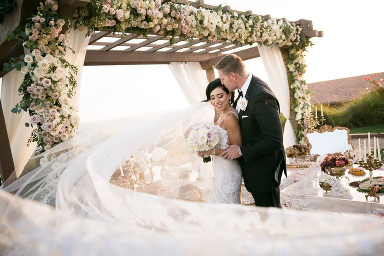 bride and groom in front of flower-decked chuppah with wind-blown veil