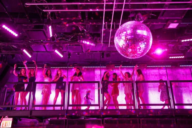 girls on warehouse balcony with pink uplighting and disco balls