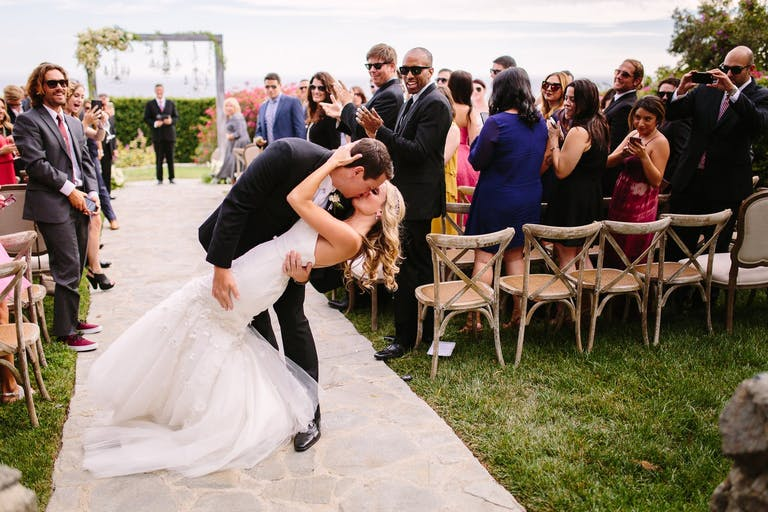 bride and groom kissing as they leave wedding ceremony