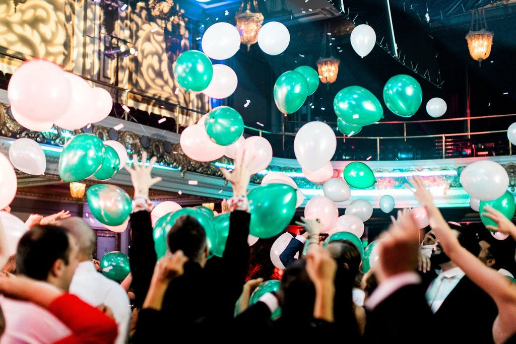 Green-and-white balloon drop over dancing guests
