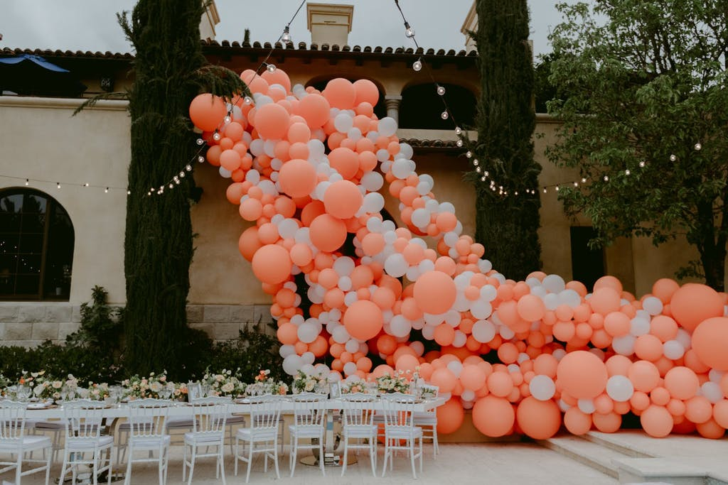 Cascading coral balloon installation in courtyard at a wedding rehearsal dinner party   PartySlate