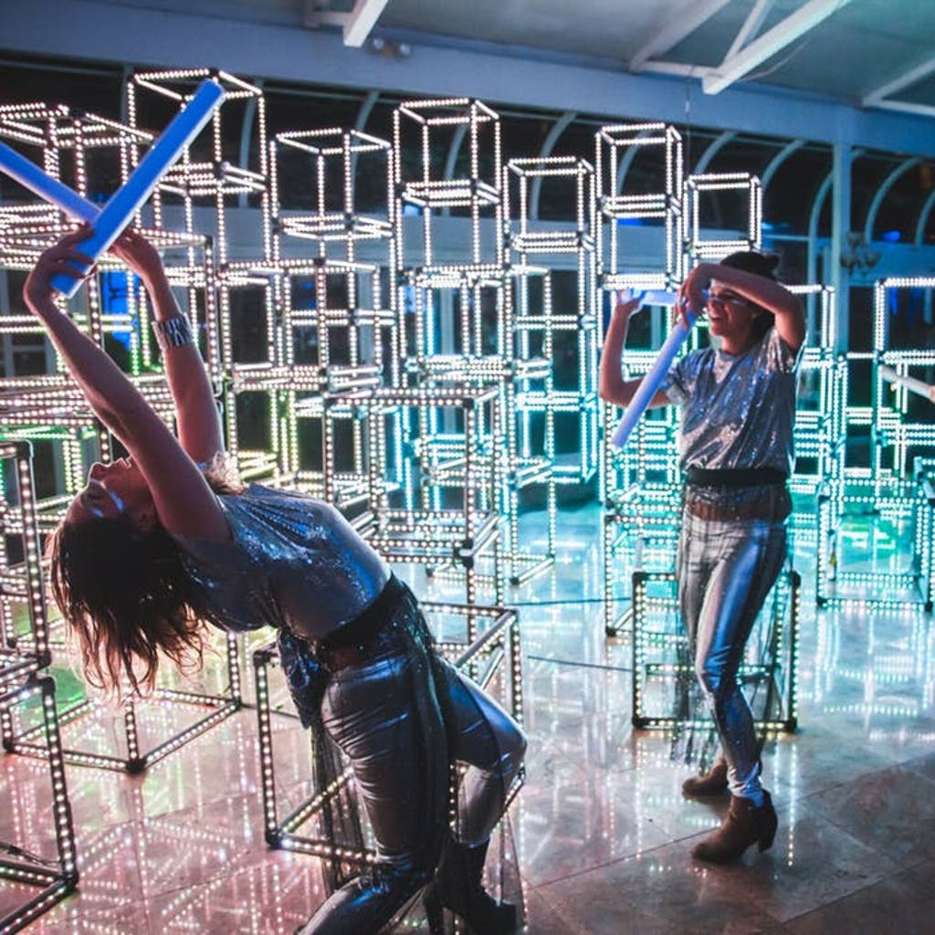 Pillars of cubes stacked together are in the background of 2 people dancing.