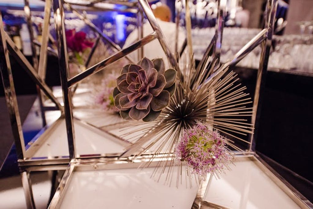 A geometric floral holder contains a succulent and a spiky circular accent piece.