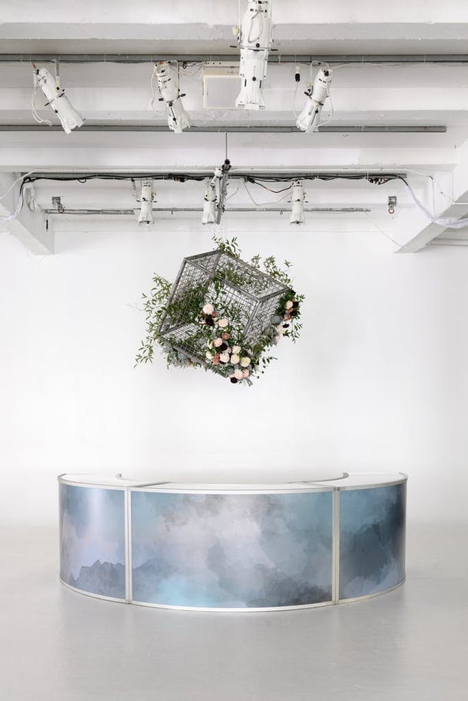 a white raw space with a galaxy patterned reception table against a white wall.. A black cube cage hangs above with greenery and pink florals.