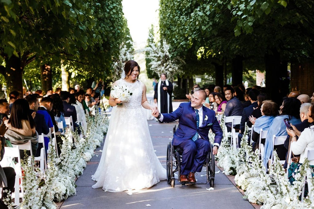 A bride and a groom in a wheel chair walk down the aisle. the aisle is lined with white florals and trees on the outside perimeter.