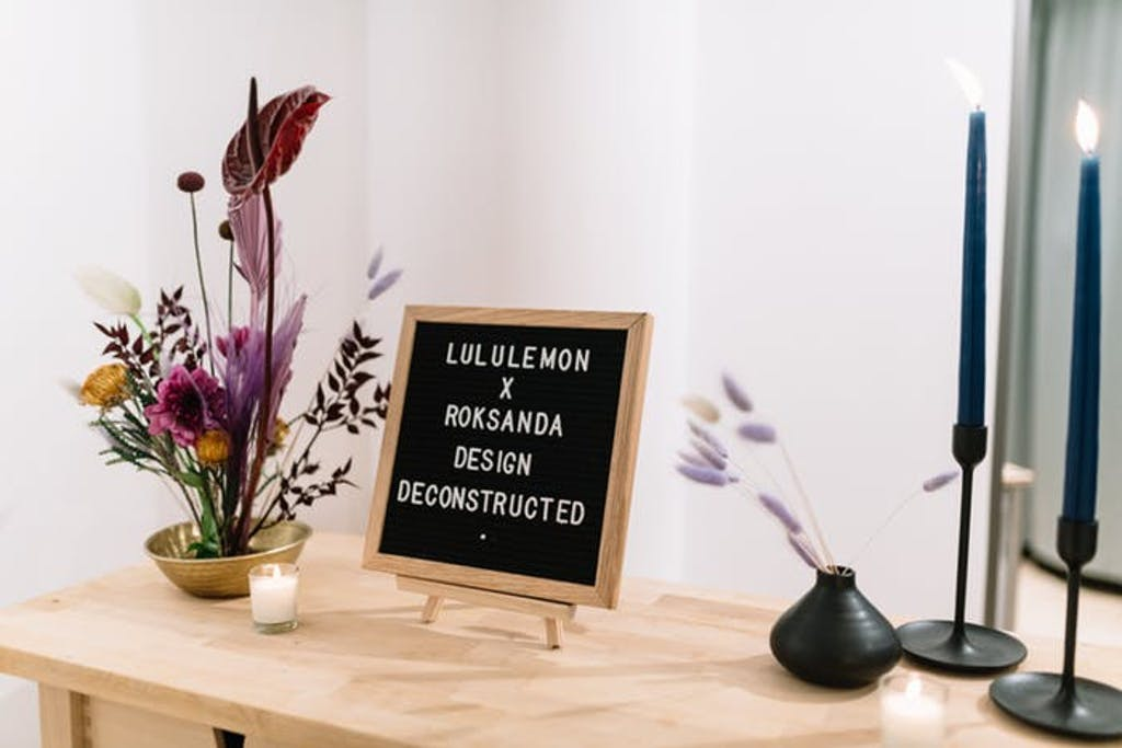 a sparse flower arrangement next to a letter sign with two pillar candles atop a light wooden table