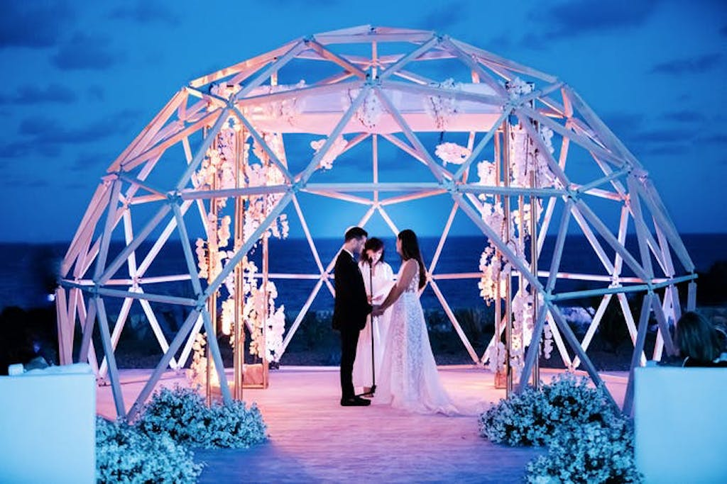 a massive igloo made out of metal encapsulates a couple holding hands at the end of the aisle.