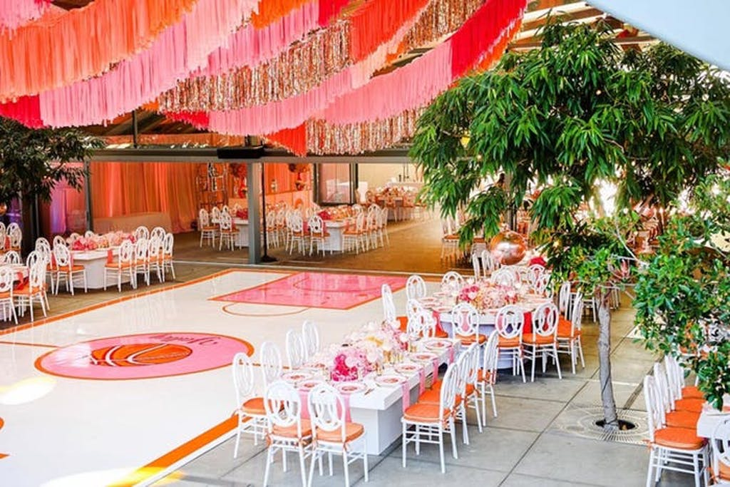 pink and silver tinsel hangs from ceiling above a white and pink basketball arena. Tables are placed next to the arena and green trees are around the perimeters