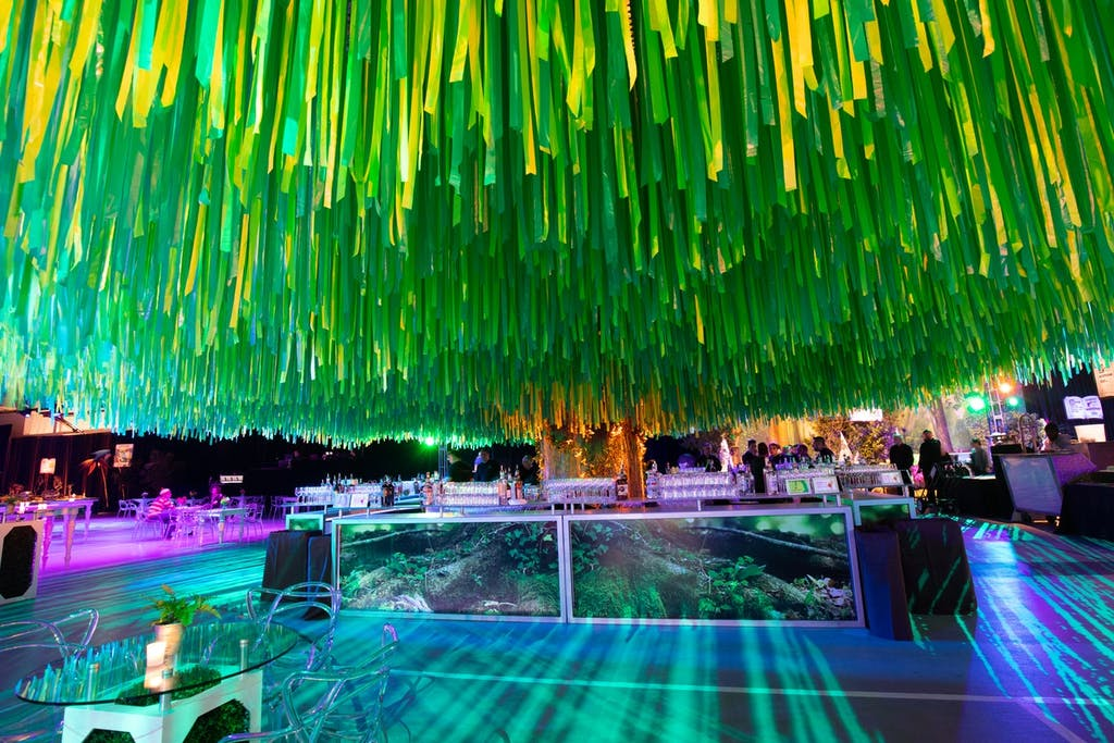 Dense green ribbon hangs from the ceiling over a colorfully lit floor and a mirrored bar.