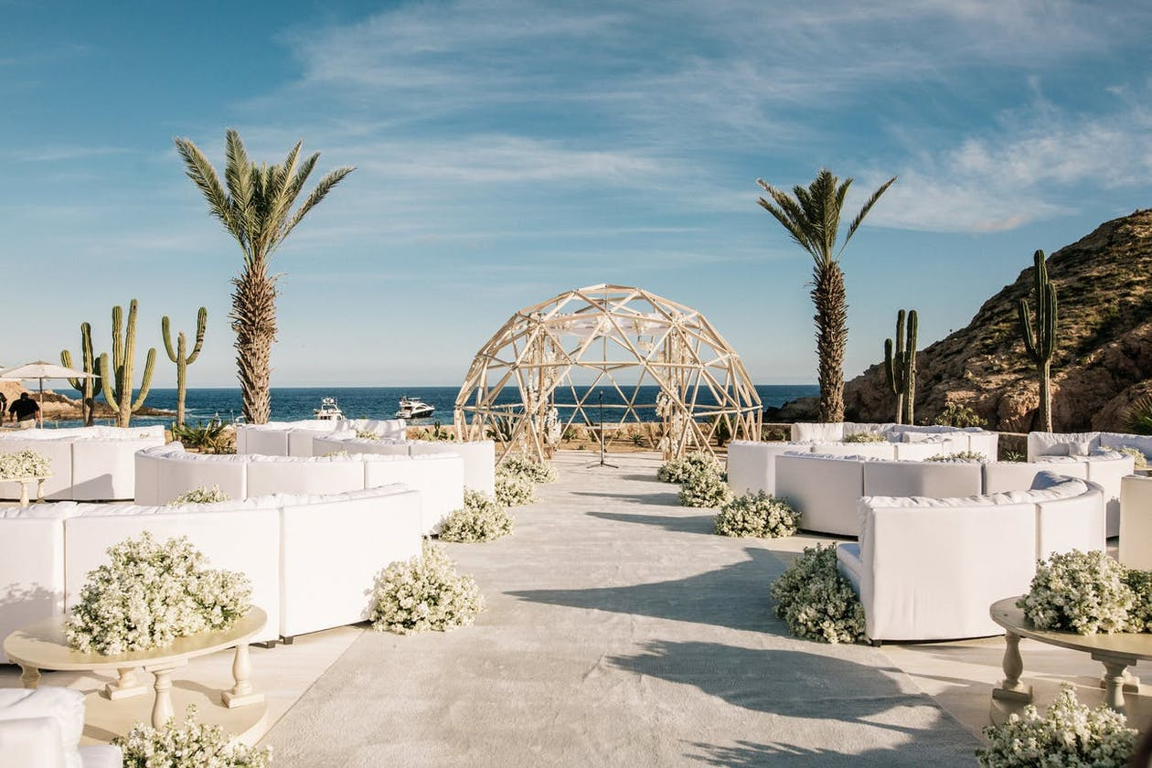 geometric wedding ceremonial arch and lounge seating against ocean backdrop