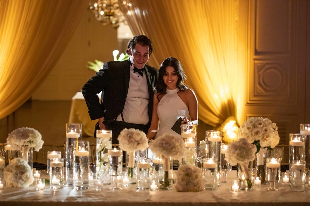 A bride and groom stand at the table admiring the centerpieces and decor. Dramatic up-lit draping is in the background.