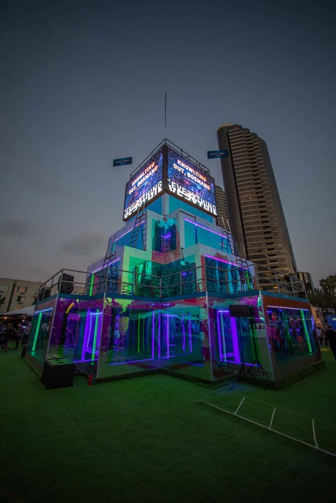 taking place on a terrace in a city, LED screens are on top of a tower and colored screens are staggered on the rest.