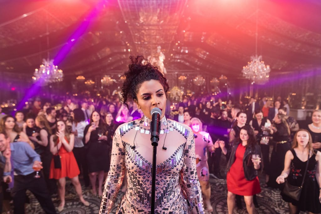 A singer stands on a stage singing with her back to the audience. chandeliers and pink lighting are in the background.