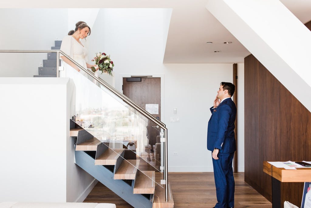 A bride walks down a minimalist stairway with the groom at the bottom wiping a tear.