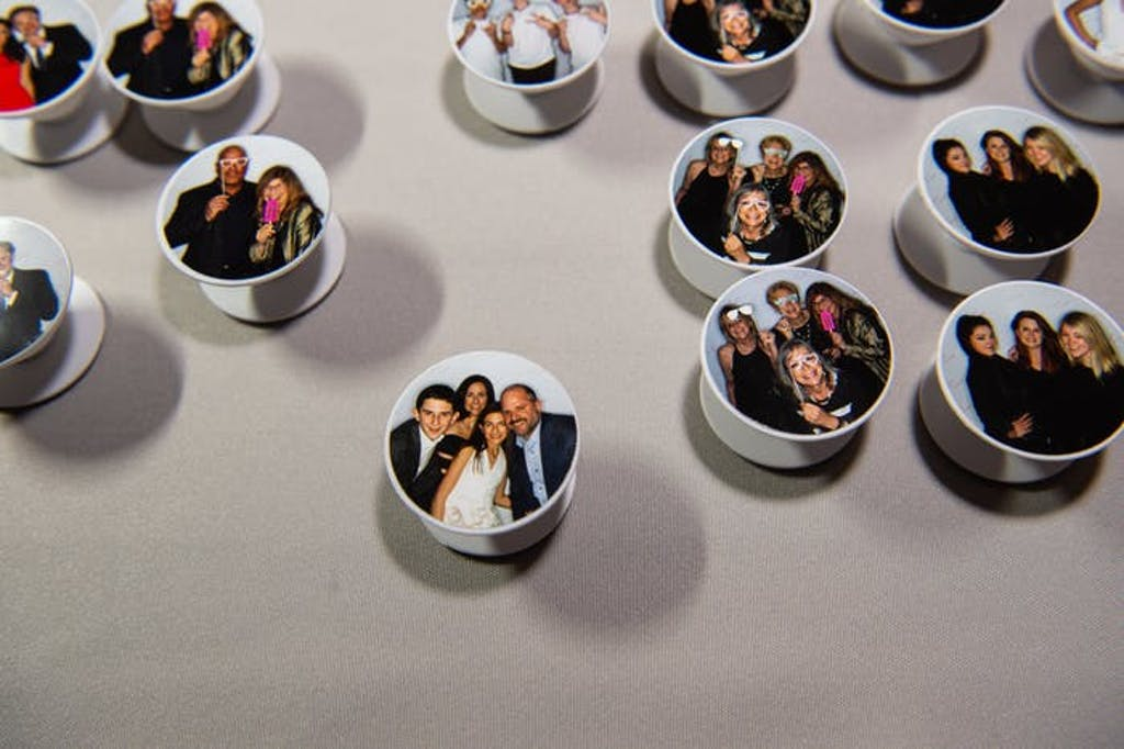 pop sockets with photo booth photos on them decorate a table.