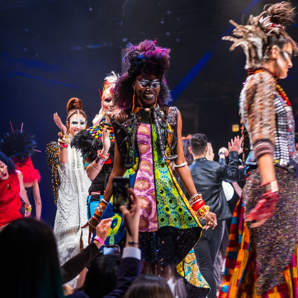 Models walk down the runway with big smiles on their faces, audience members snap pictures and clap.
