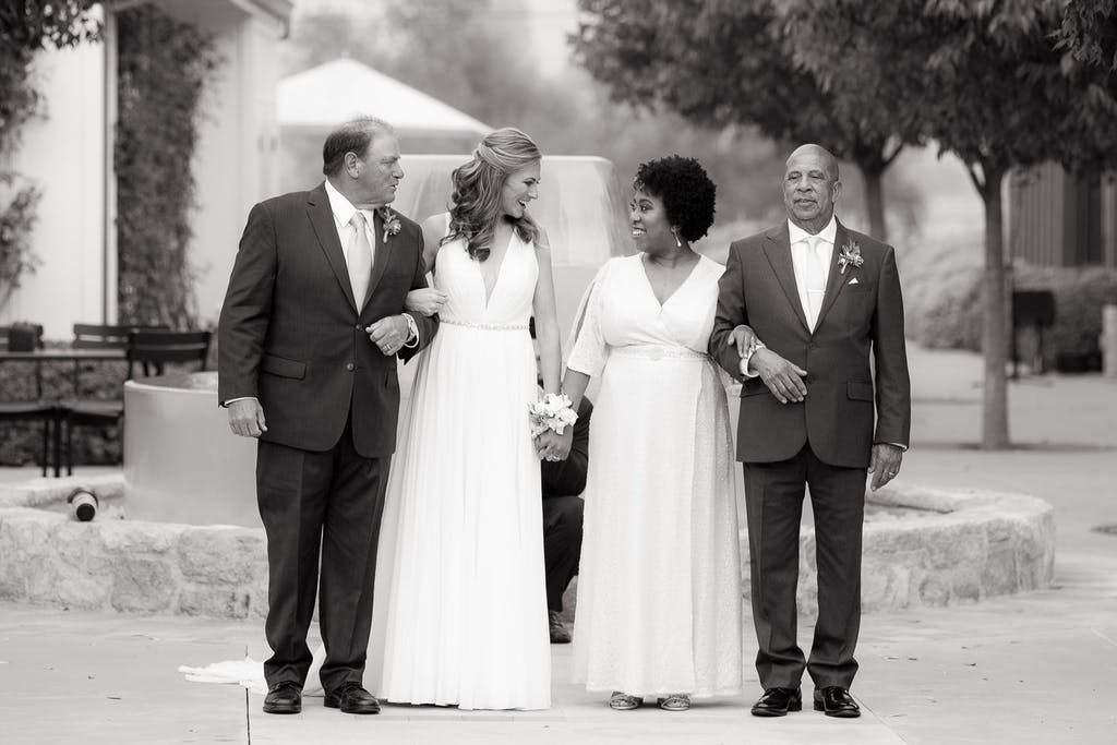 2 brides stand in the middle of each of their fathers, preparing to walk down the aisle.