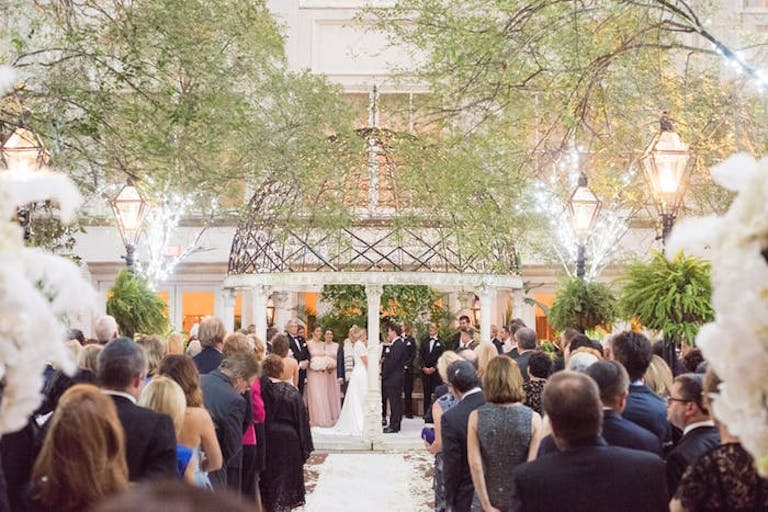 a metal gazebo above a bride and groom saying vows while family and friends watch