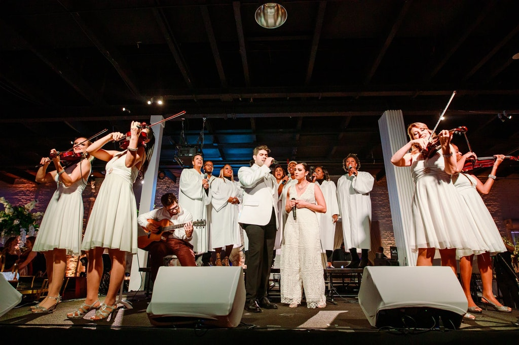 band and orchestra performing dressed in all white
