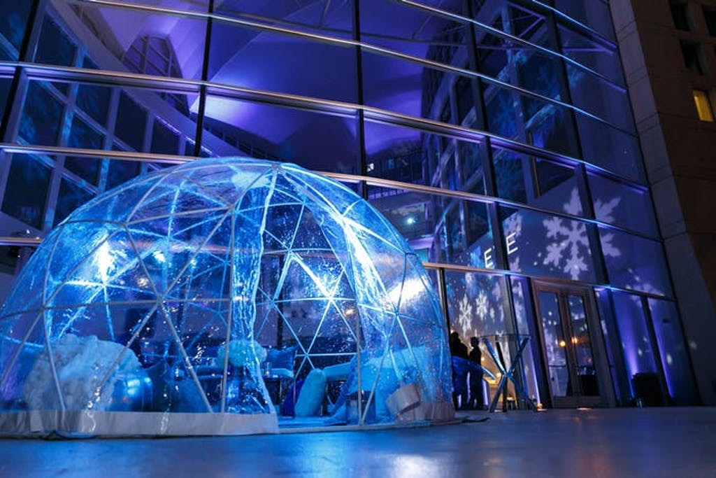 transparent igloo is lit up by blue lights in front of a wall of windows.