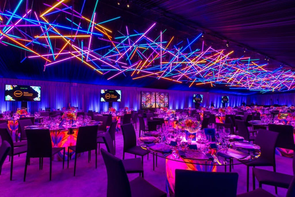 geometric blue, orange and pink neon lights act as a ceiling. Tables and chairs are lit up pink and walls are lit up purple.