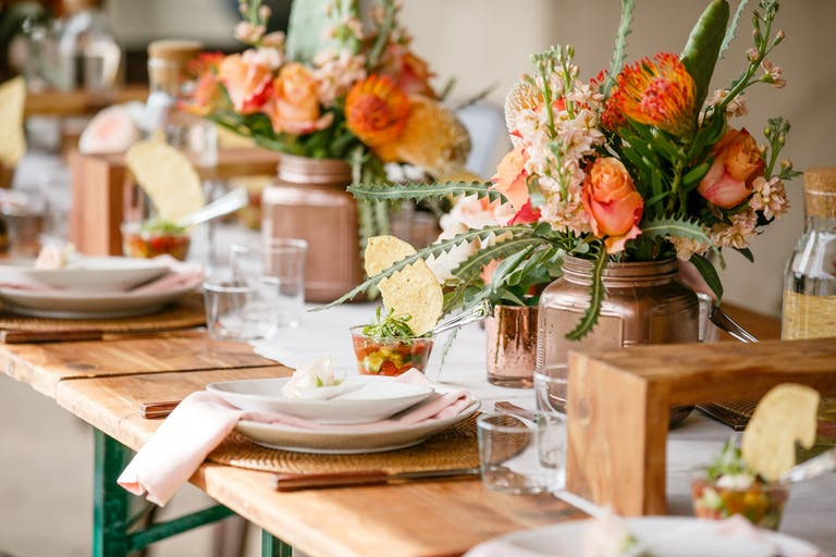 banquet table with coral-colored blooms and salsa cups