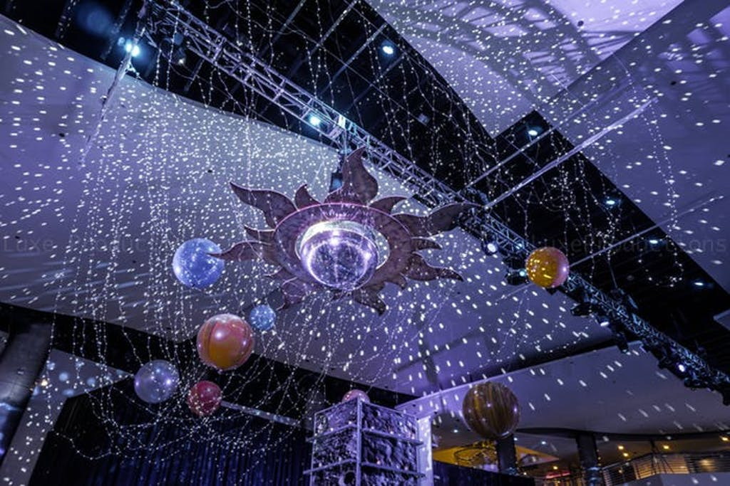 a solar system hangs above the crowd with silver tinsel around simulating a star filled sky.
